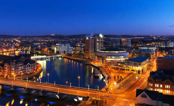 View over Belfast at night time showing brightly lit buildings reflected in the river/