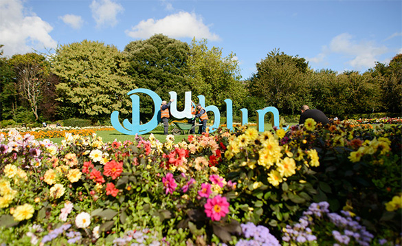workmen erecting large blue letters to spell Dublin onto a lawned area with flower borders/
