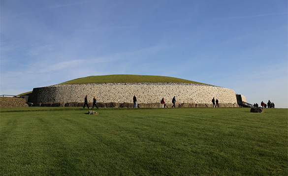 People walking past a large stone monument with grassed roof/