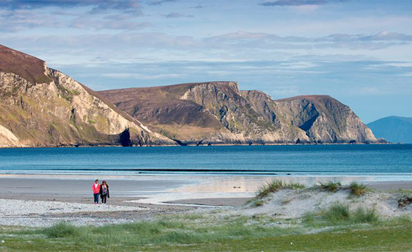 two people walking across a sandy beach by the sea with mountains in the background/