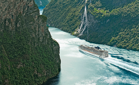 MSC Cruise ship Splendida cruising up a fjord in Norway beside a waterfall/