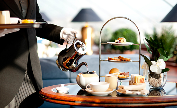 Butler serving afternoon tea in the MSC Yacht Club/