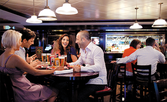 Passengers chatting over drinks and a meal onboard a NCL cruise ship/