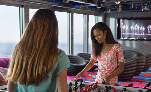 Two girls playing table football onboard a NCL cruise ship/