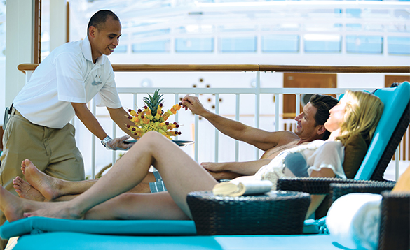 Waiter serving fruit to a couple on sun loungers on board a NCL cruise ship/
