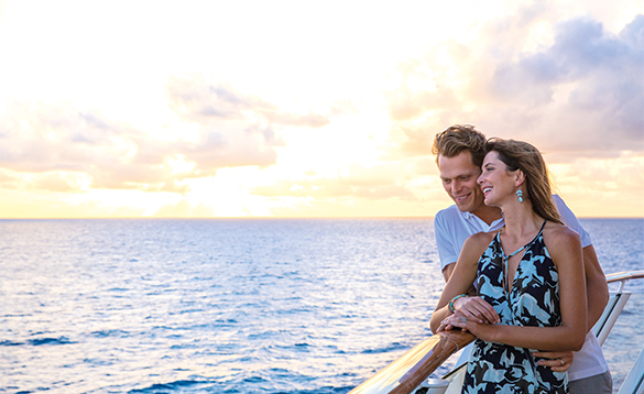 Couple standing at a balcony watching the sunset onboard a NCL cruise ship/