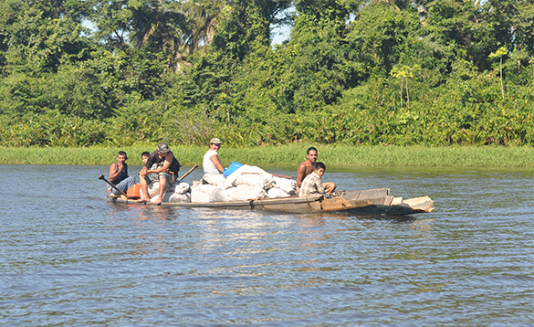Group of Nicaraguan people on a local raft transporting white sacks along a river/