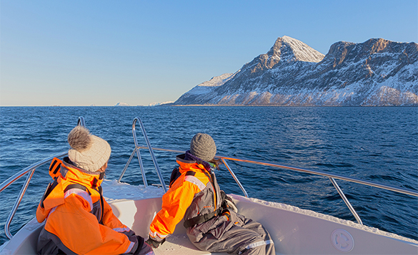 Couple on a boat cruising along the coast of northern Norway/