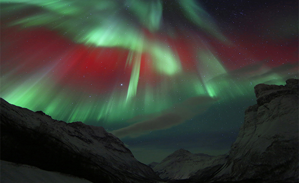 Red and green northern lights over mountains in northern Norway/