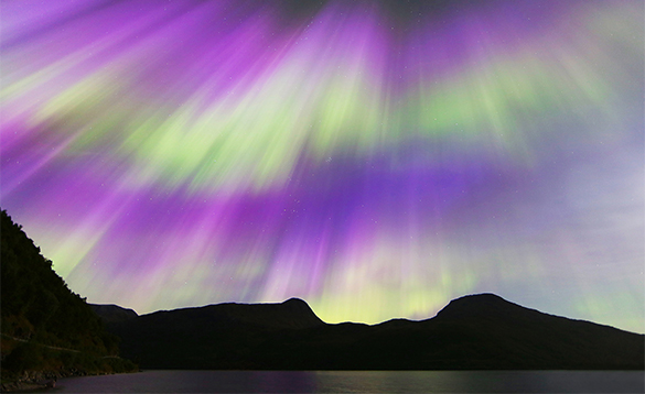 Purple and green northern lights over mountains in Norway/