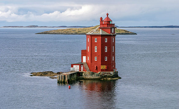 Large red painted lighthouse on an island /