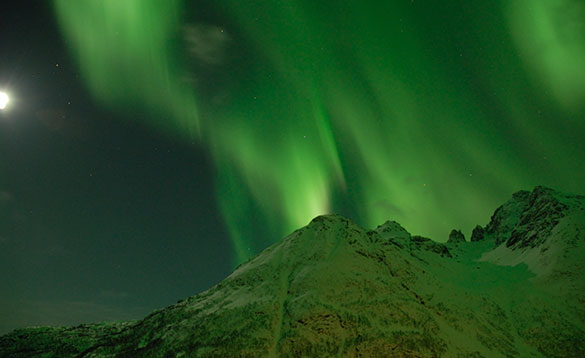 green northern lights reflecting in the snow on a mountain top/