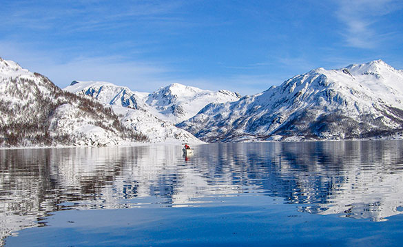 man on a rowing boat in the middle of a fjord with snow covered mountains in the background/