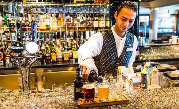 Barman serving drinks in the Azura bar on a P&O Cruises ship/