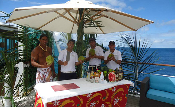 Staff serving drinks at a Coconut Bar on a Paul Gauguin cruise ship/