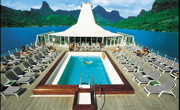 Guests on a Paul Gauguin cruise ship relaxing by the pool/
