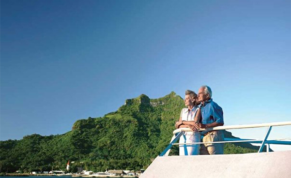 Couple standing against a balcony enjoying the views from a Paul Gauguin cruise ship/