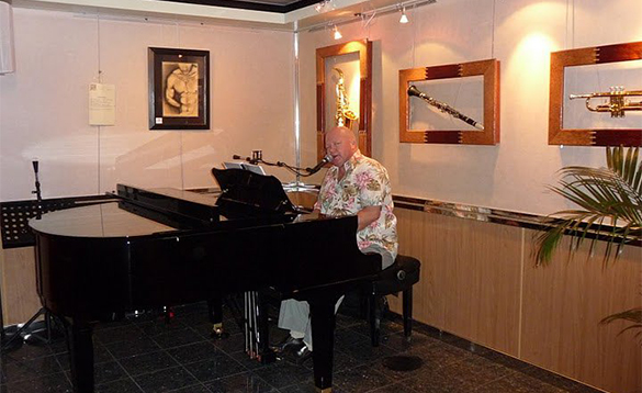 Man playing a piano in the Paino Bar on a Paul Gauguin cruise ship/