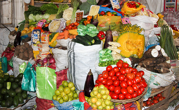 market stall with displays of lots of fruit and vegetables/