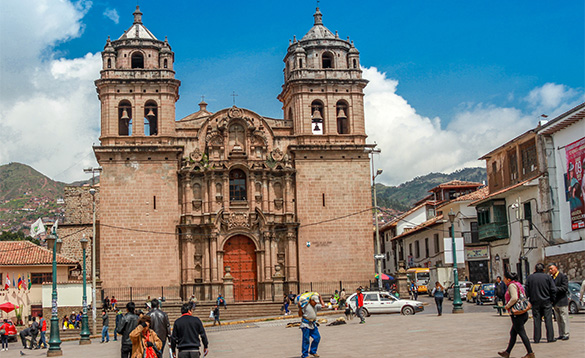 looking across a town square in Peru towards a brick built church with arched entrance between two tall bell towers/