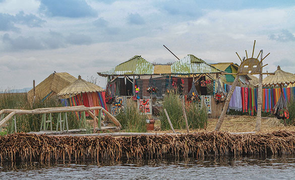 tin Peruvian huts with brightly coloured fabrics hanging on washing lines/