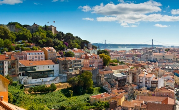 view across Lisbon towards a tree covered hill with a castle on top/