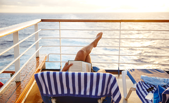 Lady laid on a sunlounger reading a book on the deck of a Princess cruises ship/