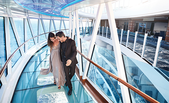 Couple walking around a glass bottomed pathway - the Seawalk on Princess Cruises ship/