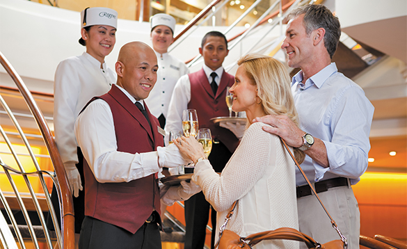 Staff on a Regent Seven Seas cruise ship welcoming passengers with drinks/