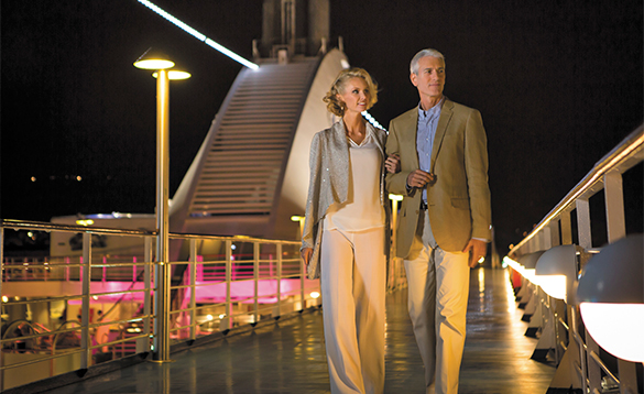 Couple enjoying a night time stroll on deck on a Regent Seven Seas cruise ship/