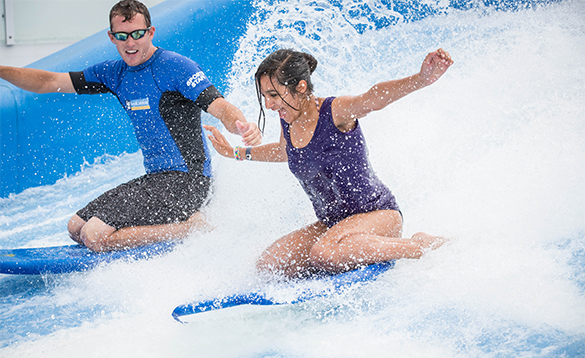 Lady and gentleman kneeling on surf boards on the Flowrider aboard a Royal Caribbean cruise ship/