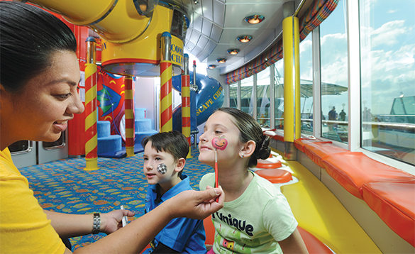 Lady face painting two children on board a Royal Caribbean cruise ship/