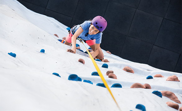Lady climbing the Rockwall on a Royal Caribbean cruise ship/