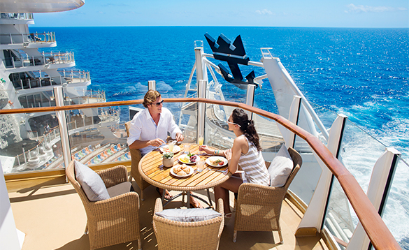 Couple eating breakfast on the balcony of their cabin aboard a Royal Caribbean cruise ship/