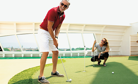 Couple playing golf aboard a Seabourn cruise ship/