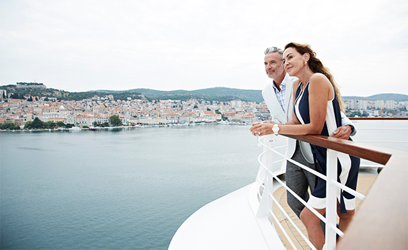 Couple standing on a deck of a Seabourn cruise ship enjoying the views/