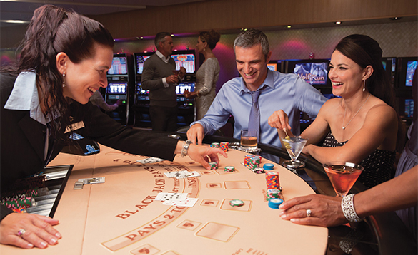 Passengers playing cards and drinking cocktails in the casino on a Seabourn cruise ship/
