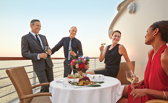Group of friends enjoying drinks on their balcony aboard a Seabourn cruise ship/
