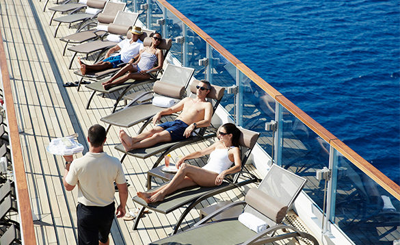 Deck hand delivering towels to passengers on sun loungers on the deck of a Seabourn cruise ship/