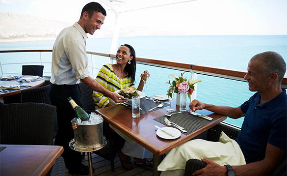 Waiter serving food to a couple dining on the Colonade Patio aboard a Seabourn cruise ship/