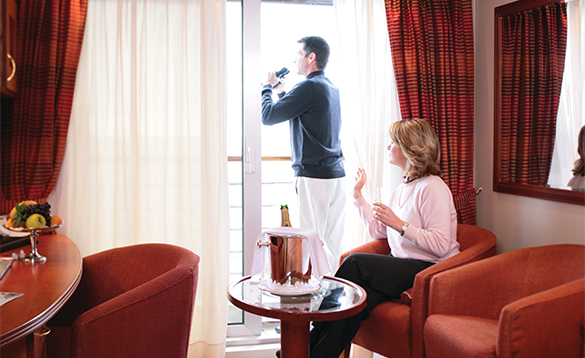 Couple taking in the views from their oceanview suite onboard a Silversea's cruise ship/