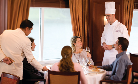 Passengers enjoying delicious food whilst chatting to the chef onboard a Silverseas cruise ship/