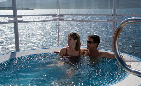 Couple relaxing in the jacuzzi enjoying the views from a Silversea's cruise ship/