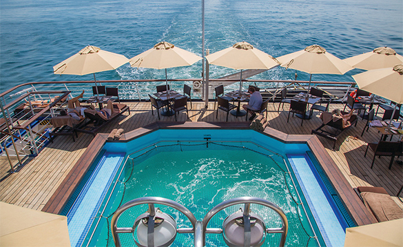Passengers relaxing by the pool onboard a Silverseas cruise ship/