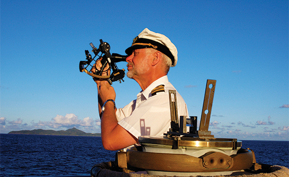 Captain navigating using a sextant on a Star Clippers ship/