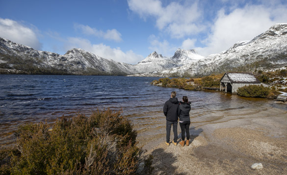 Couple stood on a lake shore with snow capped mountains surrounding it/