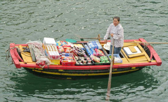 Asian lady paddling a wooden boat full of goods to sell/