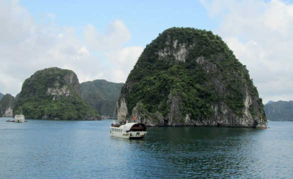 wooden boat cruising past a limestone islands topped with rainforests in Vietnam/