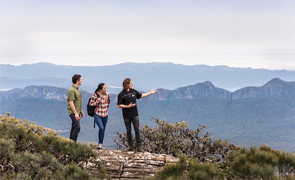 three people walking through mountains in Australia/