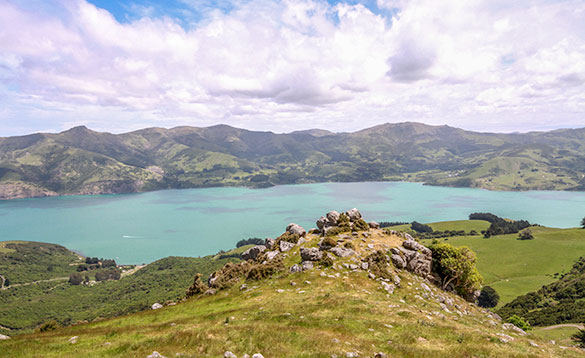 view across hills to a large blue lake surrounded by grass covered hills/